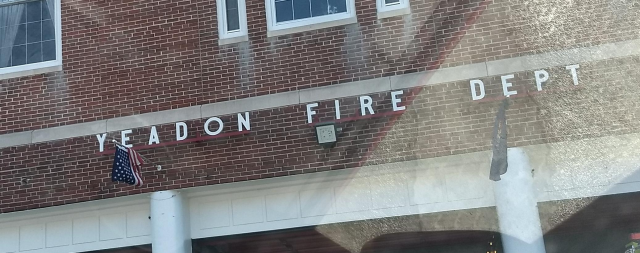 A portion of the vehicular entrance of the firehouse, which is a three-story brick-faced building displaying the flags of the U.S. and of Pennsylvania.  Bolted to racks above the main driveways are the letters YEADON FIRE DEPT.