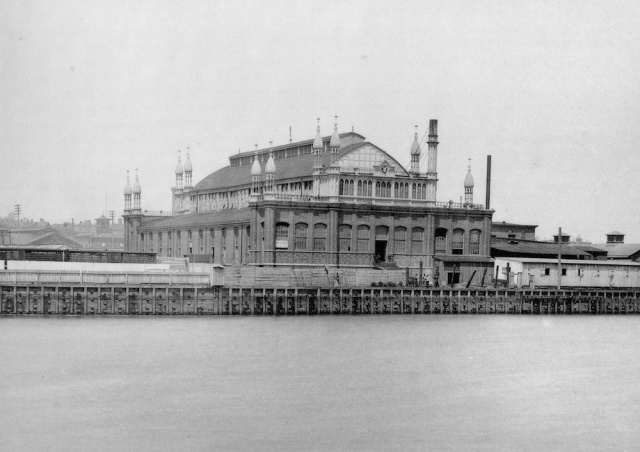 A grayscale photograph of the abattoir depicted at left.  The Schuylkill river is in the foreground.  The spires are clearly visible.  To left and right are low storage buildings.  The abattoir has one very high lower story of dark brick, surmounted by a lighter-colored cupola with tall windows and an arched roof with a skylight.