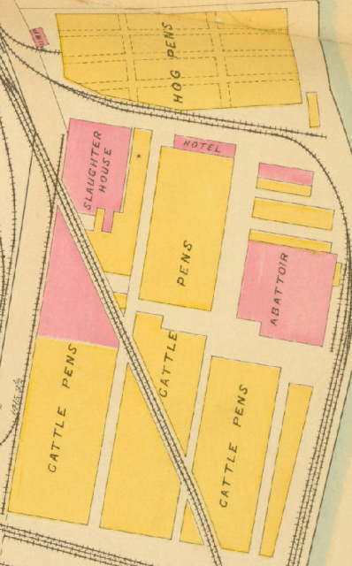 A portion of a map, with buildings marked in yellow and pink.  Several large yellow buildings, surrounded and cut through with rail lines, are labeled CATTLE PENS.  Pink buildings on the left and right are SLAUGHTER HOUSE and ABBATOIR.  In between is a smaller pink building labeled HOTEL.  Just north of the hotel are the HOG PENS.