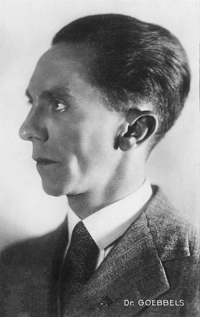 Actual archival photograph of Goebbels, in right profile, just like Mickey Mouse Goebbels in the previous picture, but from the chest up.  His mouth is closed and he is wearing a wool suit, white shirt with collar, and a wide necktie.