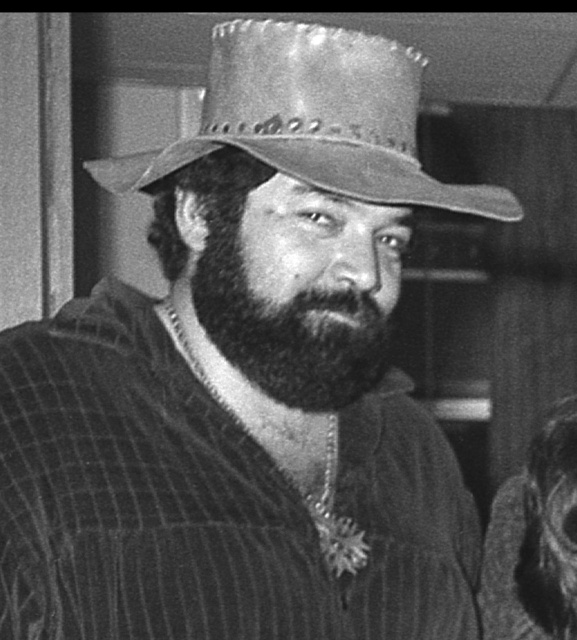 Paul L. Smith is a heavyset, slightly overwight man with a thick, curly black beard and mustache.  In this (grayscale) picture his shirt, which appears to be velour, is open at the neck, dispolaying a necklace with a large star resting among a profusion of curly black chest hair.  He is wearing a battered leather hat with a wife brim, and is looking sidelong at the camera, with a smile of amusement.