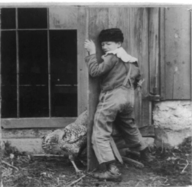 A black-and-white photograph of a young boy in overalls, with his hips pressed against a wooden door, a pained expression on his face.  On the other side of the door, there is a large chicken, with its head hidden by the door.