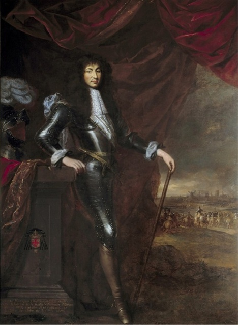 Louis as a young man.  He is standing in three-quarter profile, displaying his entire right leg. He is wearing tight black leather trousers with decorative metal studs, and tight-fitting brown leather boots.