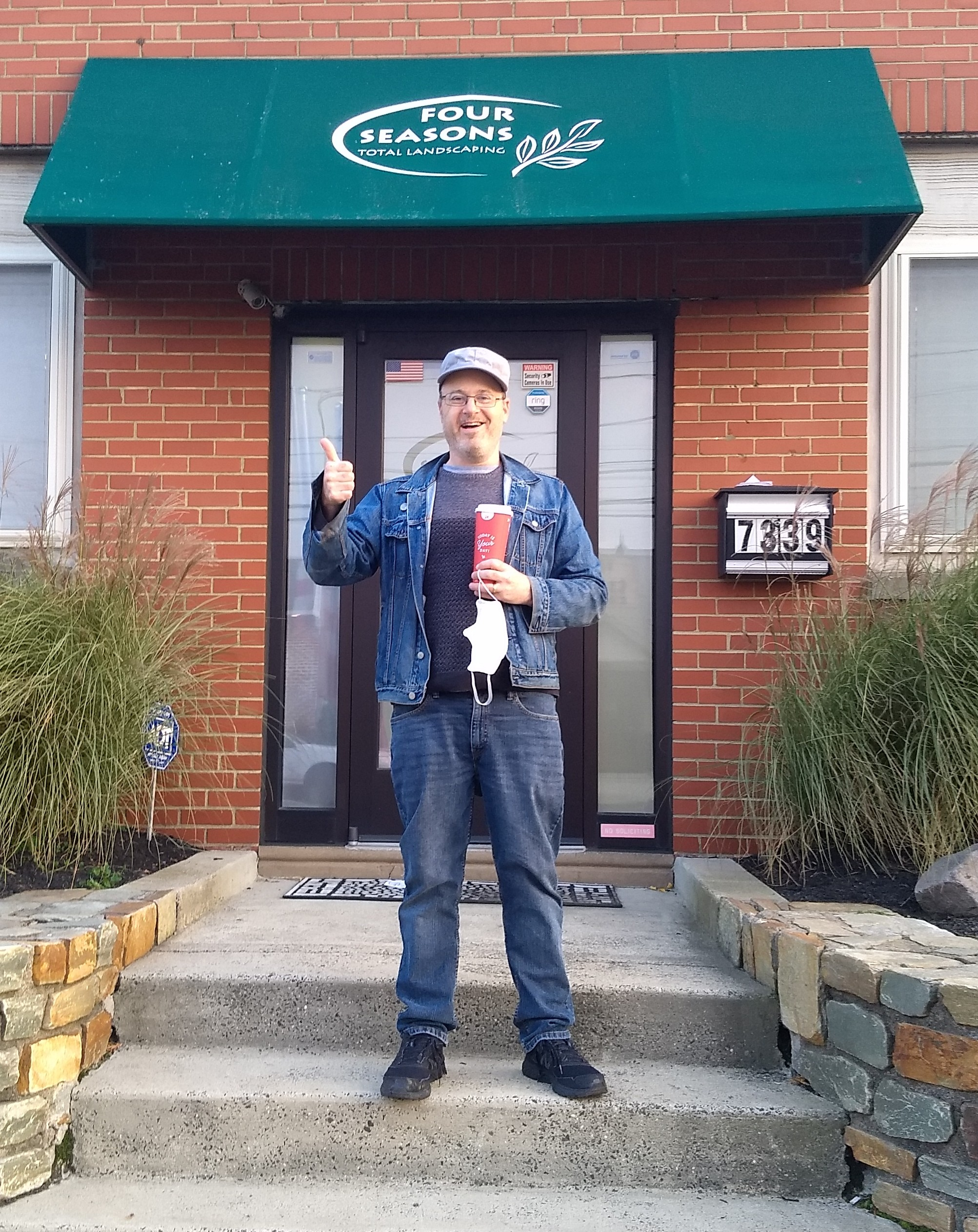 I am smiling in front of the main entrance of Four Seasons Total Landscaping in the Tacony neighborhood of Philadelphia.  I am wearing a gray cap and sweater, jeans, and a blue denim jacket.  I have a red paper Wawa coffee cup in one hand, and am giving a thumbs up with the other.