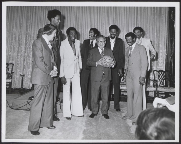 Six tall black men, members of the Harlem Globetrotters (including Meadowlark Lemon) stand in what appears to be a hotel ballroom.  In front of them is Henry Kissinger, smiling and holding a basketball with the Globertrotters' signatures.