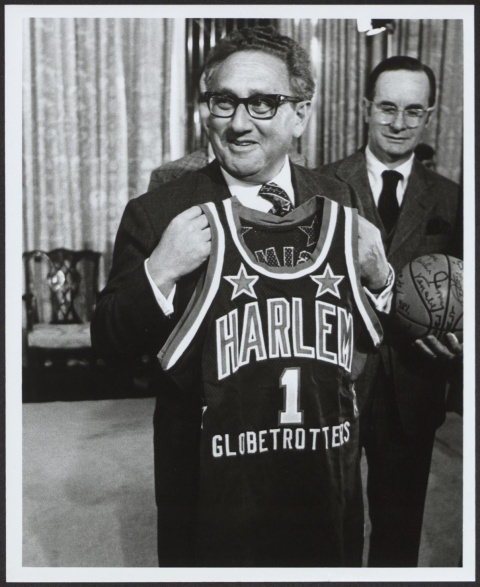 Henry Kissinger alone, smiling and holding up a Harlem Globetrotters game jersey with the number '1'.