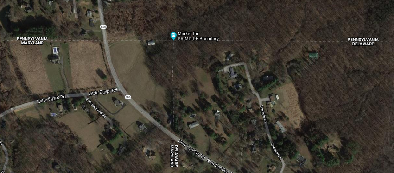 Satellite photograph of the vicinity of the tripoint.  The Pennsylvania border stretches east-west across the picture with the monument marking the place where Maryland becomes Delaware.  Route 896 crosses the border a little bit west of the tripoint.  In between these are a field and a large building of some sort.