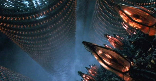 A still from the movie _The Matrix_ showing endless ranked columns of translucent pods, each containing an inert human body.