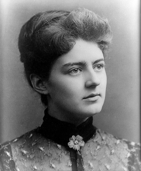 Frances Folsom Cleveland, age 21.  This is a grayscale photograph of a light-skinned woman with dark hair cut short, with a poof over the forehead.  She has light-colored eyes and a strong chin with a slight dimple.  She is wearing a blouse with an embroidered tulle overlayer, a black velvet collar, and a jeweled five-petaled brooch at her throat in the shape of a flower.