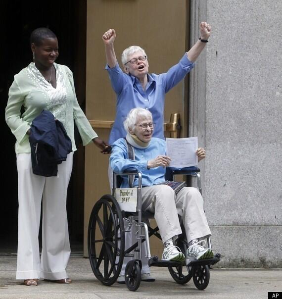 Two elderly women with white hair, both smiling.  One is seated in a wheelchair, holding up an official-looking certificate.  The other has her arms raises in triumph.  A third woman stands beside them, smiling.