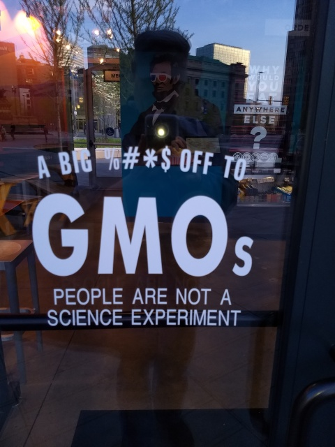 "A glass restaurant door with the message ""A BIG %#*$ OFF TO GMOs / PEOPLE ARE NOT A SCIENCE EXPERIMENT"""