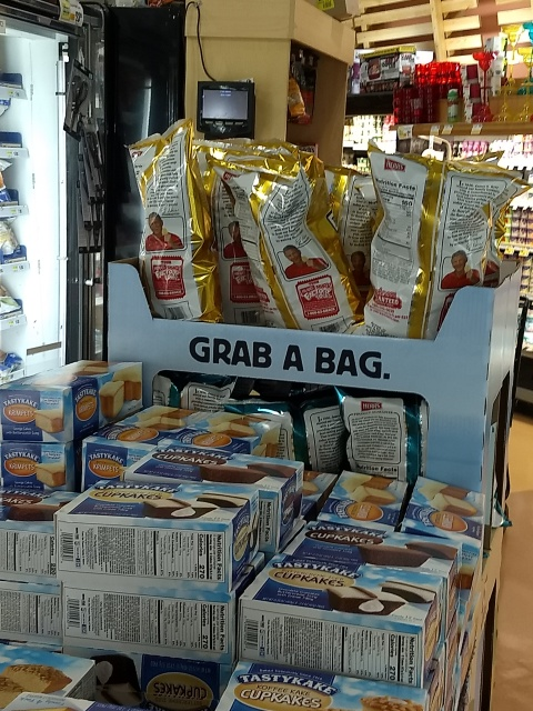 "A sign on a supermarket display of potato chips that says ""GRAB A BAG"""