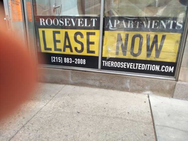"A window sign that says ""ROOSEVELT APARTMENTS LEASE NOW"""