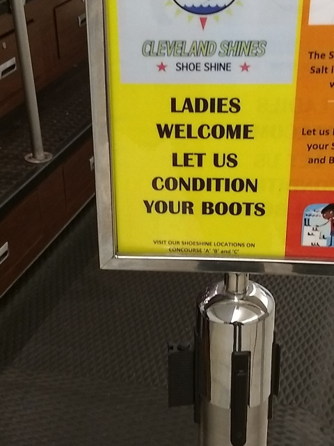 "A placard that says ""LADIES WELCOME LET US CONDITION YOUR BOOTS"""