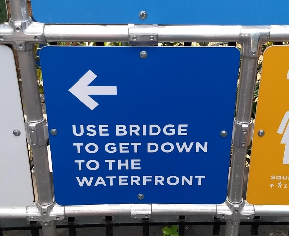 "A blue directional sign that says ""USE BRIDGE TO GET DOWN TO THE WATERFRONT"""