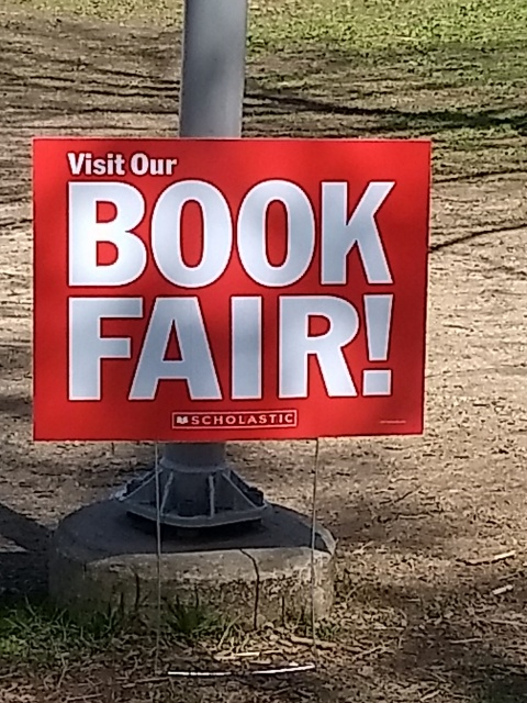 "A lawn sign that says ""Visit Our BOOK FAIR!"""