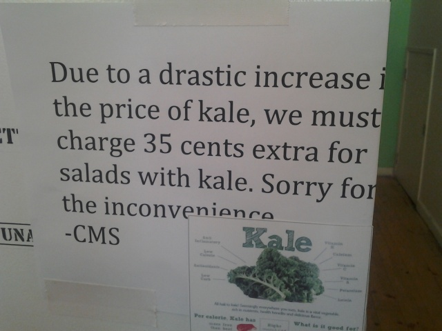 "Photograph of a sign that says ""Due to a drastic increase in the price of kale, we must charge 35 cents extra for salads with kae.  Sorry for the inconvenience.  -CMS"""