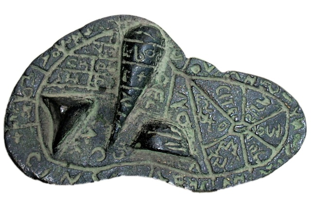 A bronze artifact in the shape of a sheep's liver, with lobes visible. The surface is mostly flat, but with three geometric protrusions representing anatomic features of the liver. Grooves divide the surface of the artifact into labeled regions.  The labels are incised into the bronze, and are in Etruscan script.