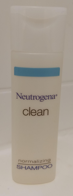 "A small bottle of hotel shampoo, labeled ""Neutrogena® CLEAN normalizing shampoo"""
