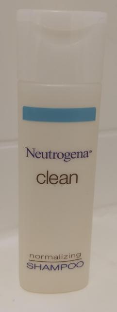 "A small bottle of hotel shampoo, labeled ""Neutrogena® CLEAN normalizing shampoo"""