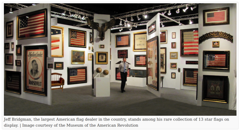 "A man stands in a museum gallery.  On the walls are many framed political posters and U.S. flags.  The caption reads ""Jeff Bridgman, the largest American flag dealer in the country, stands among his rare collection of 13 star flags on display."""