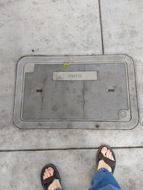 A concrete utility hole cover in a sidewalk.  My feet, wearing sandals, are also visible.  The cover is labeled 'SMFO'