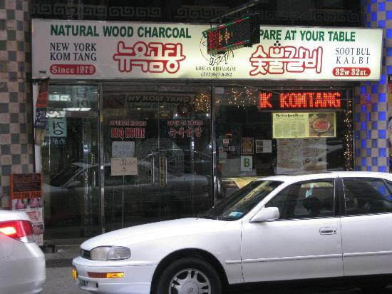 The storefront of a New York restaurant. It has a white sign with English 'NATURAL WOOD CHARCOAL PREPARE AT YOUR TABLE' in green, and Korean 'Nyuyeok gomtang sootbool galbi' in red Hangul script