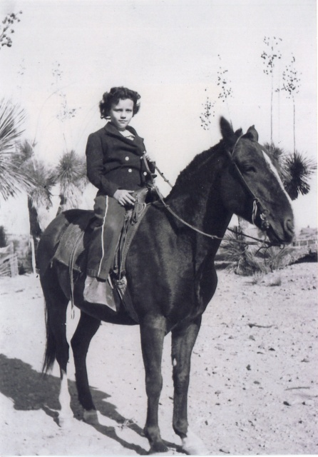 A black-and-white photograph of a young girl, perhaps eight years old, astride a pony. Her dark curly hair is cut short.  She is wearing a dark double-breasted wool jacket and loose trousers, andfaces the camera confidently.