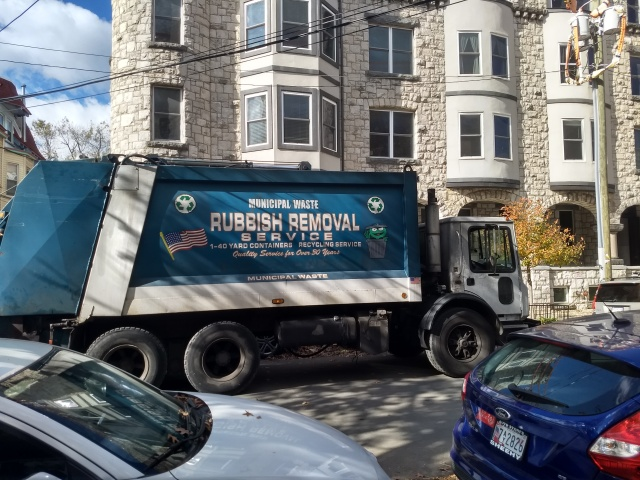 """The side of a blue trash truck, proclaiming """"MUNICIPAL WASTE"""", """"RUBBISH REMOVAL"""", and """"RECYCLING SERVICE"""".  The truck is also emblazoned with three-arrow recycling symbols, a waving U.S. flag, and a portrait of a cheerful-looking Oscar the Grouch emerging from his trash can."""