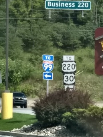 Directional signs by the side of a road, offering directions to U.S. Routes 220 and 30, and to Interstate 99.