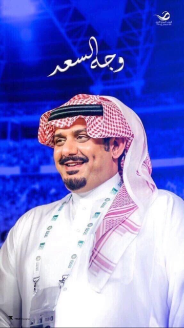 A smiling, shiny-cheeked Arabian man in middle age, with a black mustache and goatee.  He wears a very typical red-and-white checked head scarf (ghutra), held in place by a black double cord (igal).  The background is an indistinct view of a crowd in a sport stadium, in monochrome royal blue.