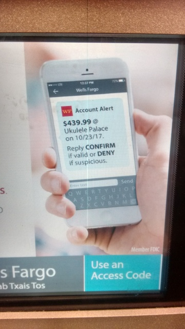 A phone displaying a Wells Fargo 'Account Alert' about a charge of $439.99 at 'Ukulele Palace'