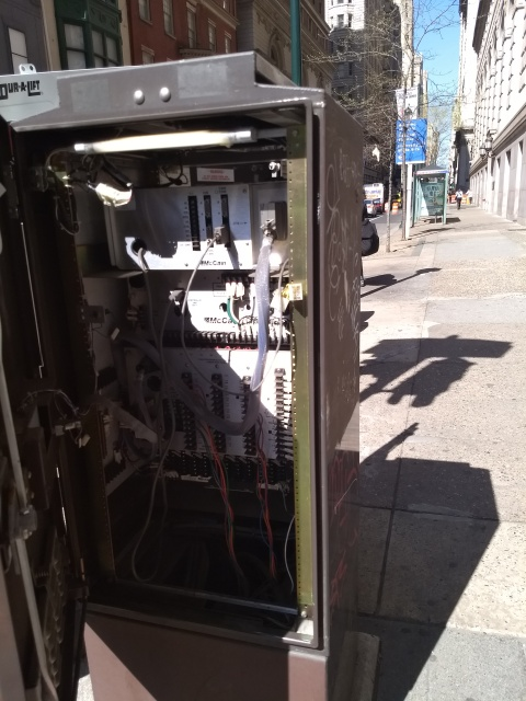 A brown metal cabinet, about six feet high, filled with some sort of electronic equipment. The equipment is modular.  Some modules have data sockets, some with cables plugged in; others look like switchboards with colored wires.