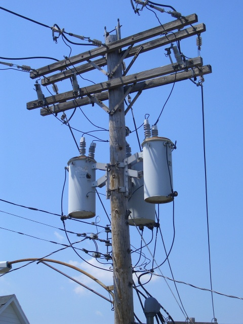A wooden power utility pole, including cobra-head street light, with three large gray cylinders mounted on it under the main wires